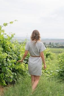 Vista posteriore di una donna in abito estivo che cammina attraverso il vigneto