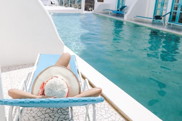 Vista posteriore di una donna con cappello estivo sdraiata su una sedia rilassante per prendere il sole in piscina