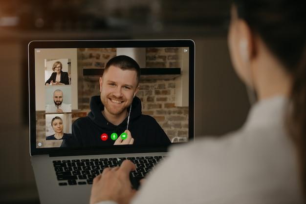 Punto di vista posteriore di una donna che parla con un socio commerciale e colleghi in una videochiamata su un computer portatile. l'uomo parla con colleghi in una conferenza webcam. squadra multietnica di affari che ha una riunione online