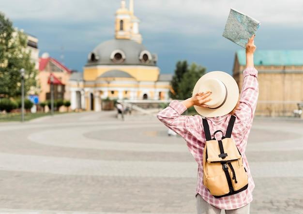 Donna di vista posteriore che viaggia in un nuovo posto