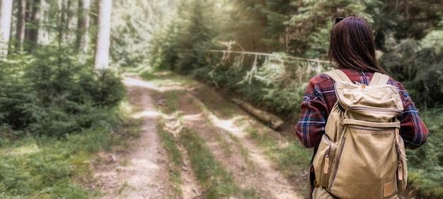 Donna vista posteriore cammina con zaino in spalla nel concetto di stile di vita di viaggio foresta