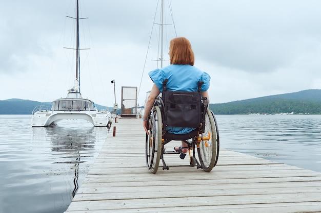 Vista posteriore di una donna su una sedia a rotelle che si muove lungo una passerella di legno verso un catamarano