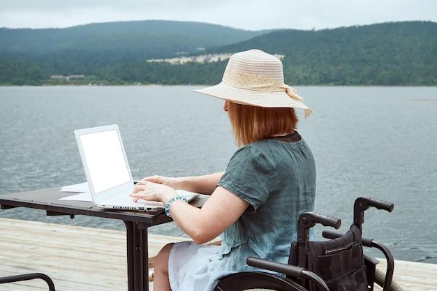 Vista posteriore di una donna su una sedia a rotelle che utilizza un computer portatile in un concetto di apprendimento del lavoro a distanza di un bar