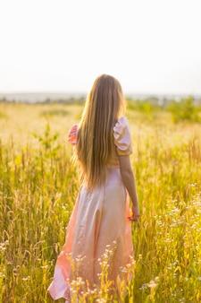 Vista posteriore di una donna con lunghi capelli biondi in piedi nel campo di fiori di campo nel lungo abito rosa.