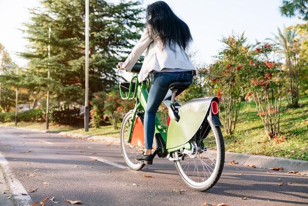 Vista posteriore di una ragazza che lavora con un en che trasporta una bici elettrica condivisa rossa lungo un sentiero alberato del parco