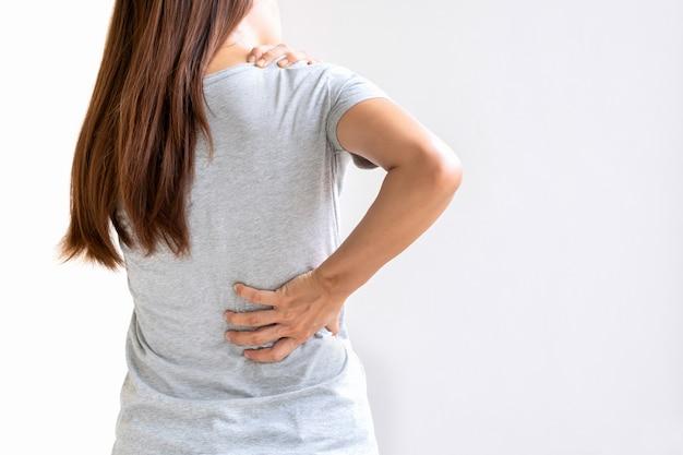 Vista posteriore della giovane donna asiatica che soffre di mal di schiena e dolore al collo isolato su sfondo bianco
