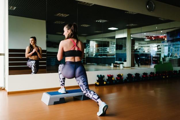 Vista posteriore giovane bella donna sexy facendo esercizi sulle natiche sulla piattaforma step in palestra vicino allo specchio