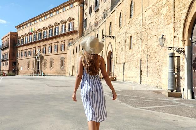 Vista posteriore di giovane bella donna che cammina vicino a palazzo reale di palermo, italia.