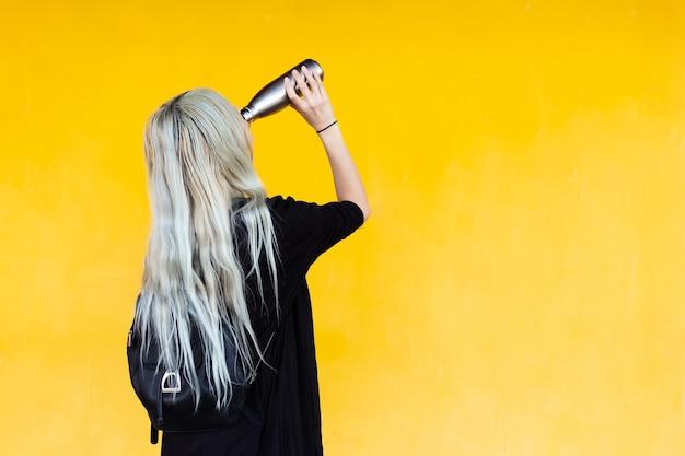 Vista posteriore di giovane ragazza bionda con zaino nero che tiene la bottiglia d'acciaio su colore giallo.
