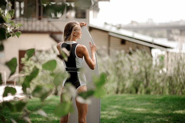 Punto di vista posteriore di giovane costume da bagno sexy biondo della donna in bianco e nero che sta con il wakeboard
