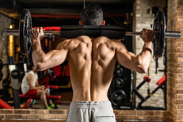 Vista posteriore del giovane bodybuilder che flette i muscoli con bilanciere davanti allo specchio in palestra
