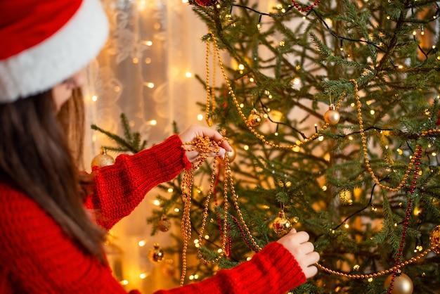 Vista posteriore di una giovane ragazza bruna che decora l'albero di abete con perline