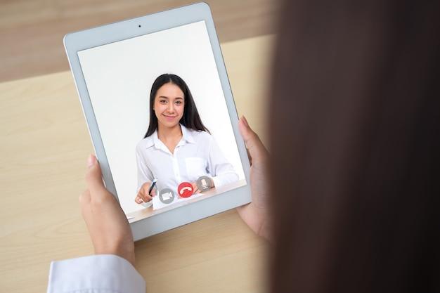 Vista posteriore del colloquio di giovane imprenditrice con candidato di lavoro con videoconferenza online