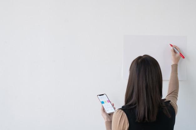 Vista posteriore di giovane imprenditrice o insegnante con smartphone ed evidenziatore in piedi dalla lavagna