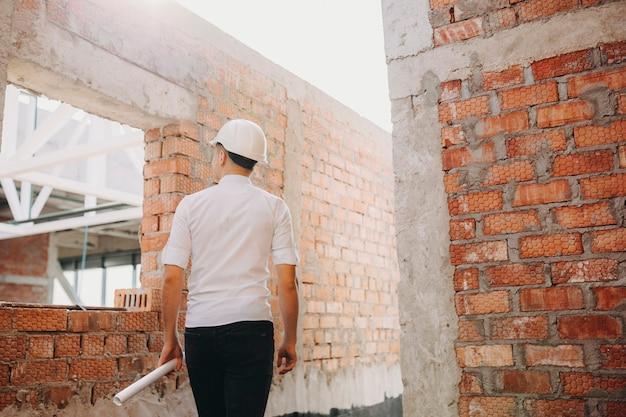Vista posteriore del giovane architetto fiducioso con un piano arrotolato in mano che cammina ispezionando il lavoro di costruzione in costruzione.