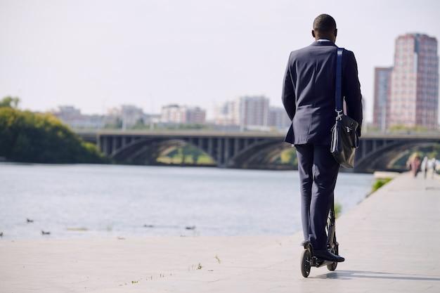 Vista posteriore di un giovane uomo d'affari elegante in abiti da cerimonia in piedi su uno scooter elettrico mentre si muove lungo la riva del fiume contro il paesaggio urbano