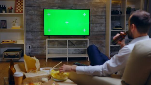 Punto di vista posteriore del giovane imprenditore che si rilassa guardando la tv. schermo verde e cibo spazzatura.