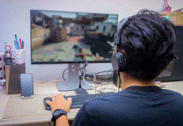 Vista posteriore del giovane giocatore che gioca con i videogiochi fps