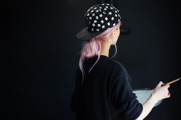 Vista posteriore della ragazza con i capelli rosa, pittura murale con pennello e colore bianco, aggiornamento dell'appartamento. indossare berretto nero e maglione.
