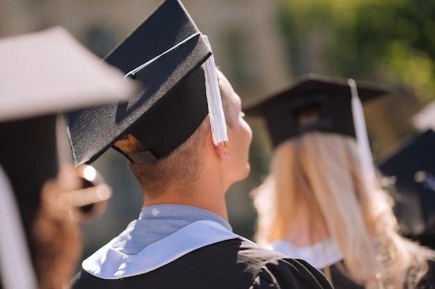 Vista posteriore di giovani laureati che indossano mantelli di maestri