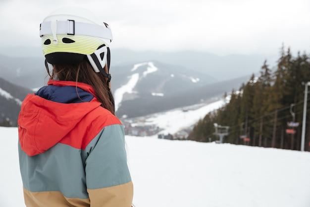 Vista posteriore della giovane donna snowboarder sulle piste gelida giornata invernale