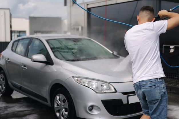 Vista posteriore del giovane che pulisce la sua auto con un autolavaggio self-service con spruzzatore a getto