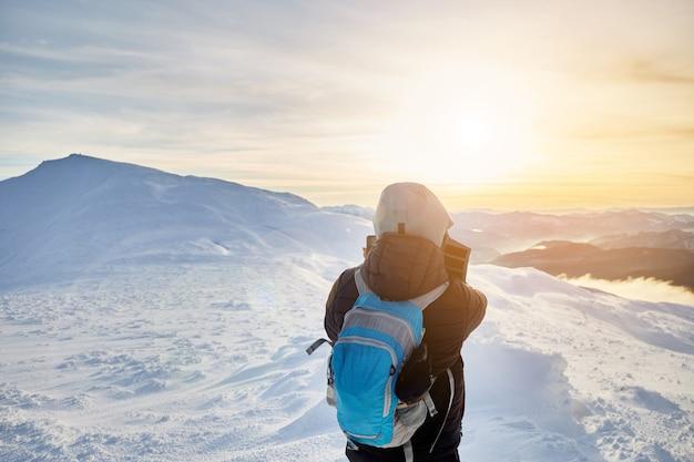 Vista posteriore del giovane che fa foto di montagne invernali