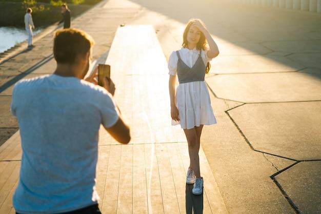 Punto di vista posteriore del giovane che prende l'immagine della ragazza sul telefono cellulare al tramonto vicino al fiume sul parco della città. felice attraente signora caucasica in posa per un fotografo maschio sullo sfondo di un raggio di sole luminoso