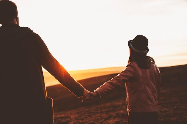 Vista posteriore del giovane e della donna che tengono le mani e camminano nel campo sullo sfondo del cielo al tramonto. anonimo coppia che cammina nella natura di sera