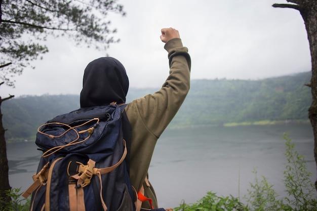Vista posteriore della giovane donna asiatica musulmana con le mani in alto in piedi sulla scogliera sul lago. concetto di viaggio, concetti di vincitore, libertà,