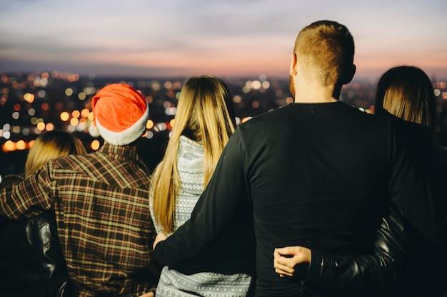 Vista posteriore di giovani che si abbracciano e ammirano la vista della città sfocata mentre si celebra il natale di notte
