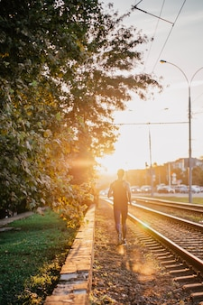 Punto di vista posteriore di giovane uomo di sport che corre lungo i camion della ferrovia contro il sole in città.