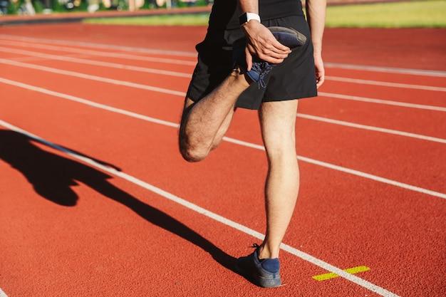 Punto di vista posteriore di un giovane sportivo che allunga gamba