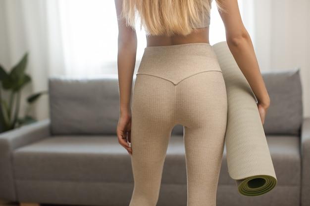 Vista posteriore della giovane donna che tiene nelle mani materassino yoga o fitness dopo aver lavorato a casa nella vita