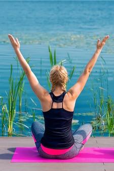 Il punto di vista posteriore della giovane donna sta facendo esercizio di yoga sull'erba della riva del lago.