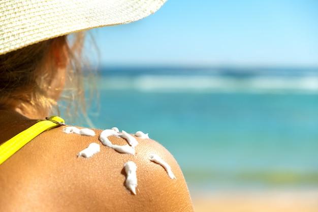 Vista posteriore della giovane donna che si abbronza in spiaggia con crema solare a forma di sole sulla spalla. protezione dalle scottature solari uv e concetto di crema solare