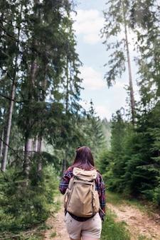 Vista posteriore giovane donna cammina con zaino in spalla nella foresta viaggi e vacanze estive concetto di stile di vita all'aperto