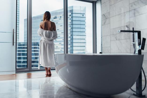 Vista posteriore della giovane donna che indossa accappatoio bianco in piedi in bagno a guardare fuori dalla finestra con vasca da bagno in primo piano.
