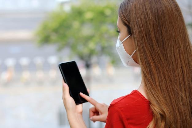 Punto di vista posteriore della giovane donna con la maschera di protezione facendo uso dello smartphone app all'aperto