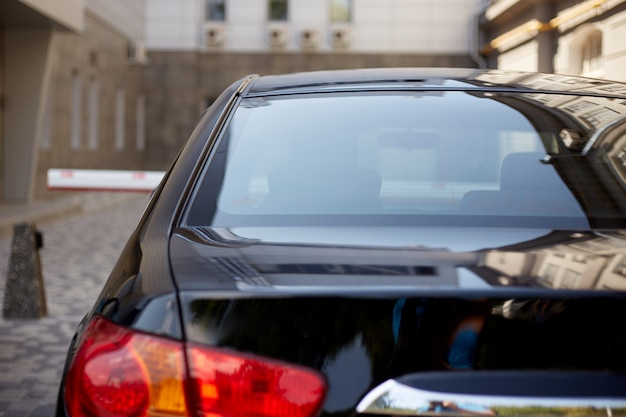La finestra posteriore dell'automobile nera ha parcheggiato sulla via nel giorno soleggiato dell'estate, retrovisione. mock-up per adesivo o decalcomanie