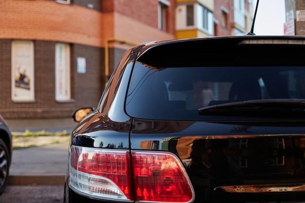 Il finestrino posteriore della macchina nera parcheggiata sulla strada in una giornata di sole estivo, vista posteriore. mock-up per adesivo o decalcomanie