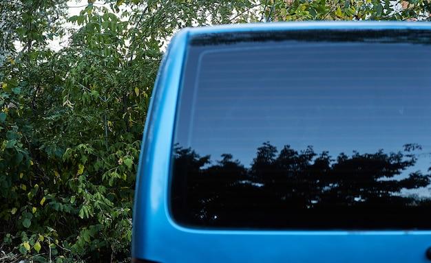 Finestrino posteriore della macchina blu parcheggiata sulla strada in giornata di sole estivo, vista posteriore. mock-up per adesivo o decalcomanie