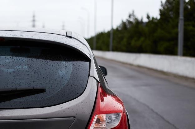 Il finestrino posteriore della macchina grigia parcheggiata sulla strada in autunno piovoso giorno, vista posteriore.