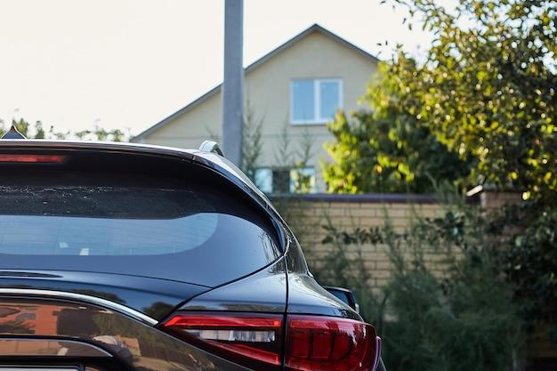 Il finestrino posteriore della macchina grigia parcheggiata sulla strada in una giornata di sole estivo, vista posteriore. mock-up per adesivo o decalcomanie