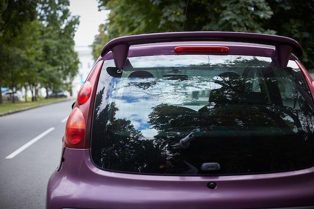 Il finestrino posteriore della macchina viola parcheggiata sulla strada nella giornata di sole estivo, vista posteriore. mock-up per adesivo o decalcomanie