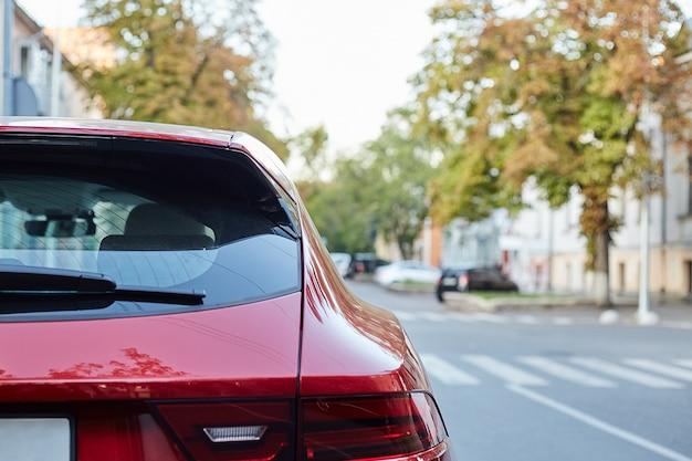 Il finestrino posteriore della macchina rossa parcheggiata sulla strada in una giornata di sole estivo, vista posteriore. mock-up per adesivo o decalcomanie