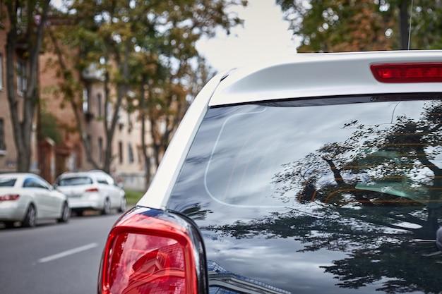 Finestrino posteriore della macchina bianca parcheggiata sulla strada in una giornata di sole estivo, vista posteriore. mock-up per adesivo o decalcomanie