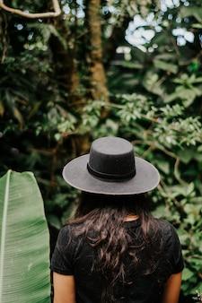 La parte posteriore di una donna che indossa un cappello in natura.