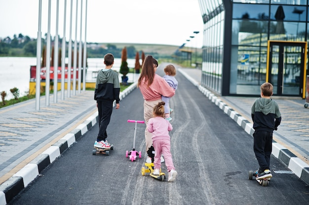 Indietro di giovane madre alla moda con quattro bambini all'aperto. la famiglia sportiva trascorre il tempo libero all'aperto con scooter e pattini.