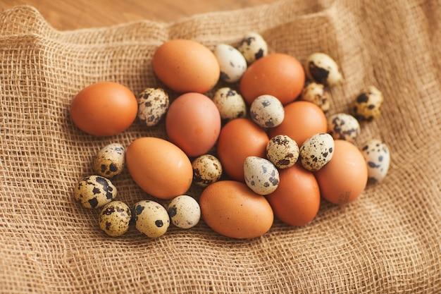 Backgroiund immagine di agricoltori uova di gallina e uova di quaglia in involucro di tela, copia dello spazio